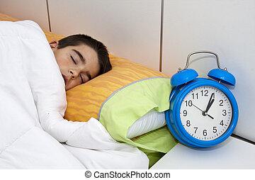 boy sleeping with alarm clock