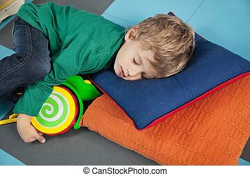 Boy sleeping With Toy In Kindergarten - Cute boy sleeping...