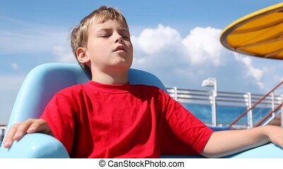 Boy sleeps in chaise lounge on ship deck in sunny weather