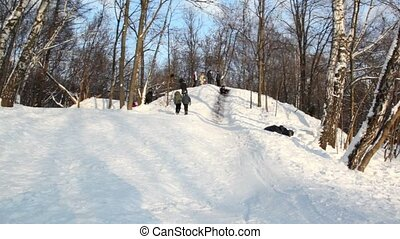 Boy slid down slope and rolled over, several people stand on hill