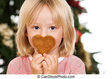 Boy smelling gingerbread cookie
