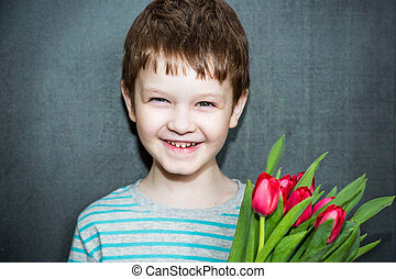 Boy smiling and holding a bouquet of red tulips.