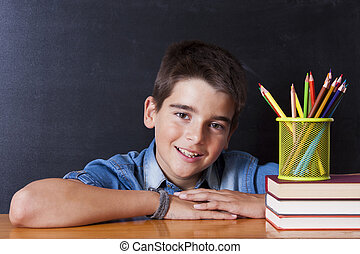 boy smiling at the table with books school