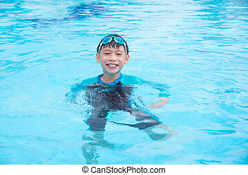 boy smiling while floating in swimming pool at a resort