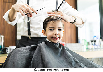 Boy Smiling While Getting Haircut By Barber In Salon