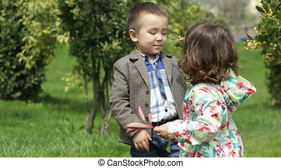 boy sniffing a sprig of a tree and kissing a girl on the cheek