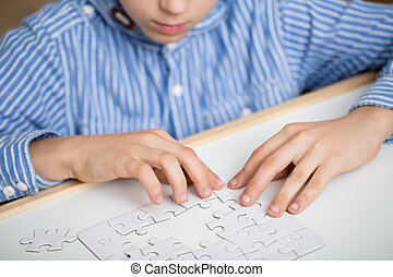 Boy solving a white puzzle - Focused little boy solving a...