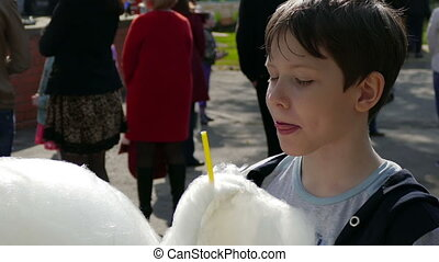 boy son eating cotton candy at the park in summer video 4k