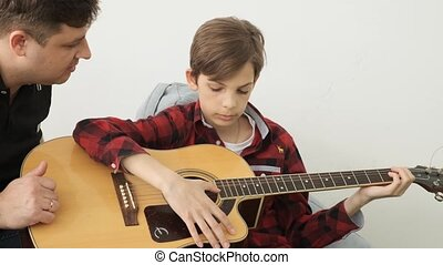 Boy spends the great leisure learning how to play guitar with his father slow motion