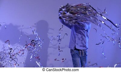 Boy spinning around with tinsel on gray background. Slow...