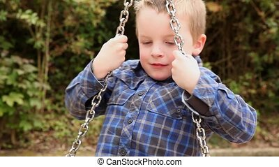Boy spinning on a swing - a 4,5 year old boy having fun on a...