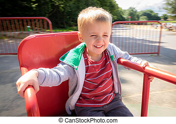 Boy spinning round on a carousel
