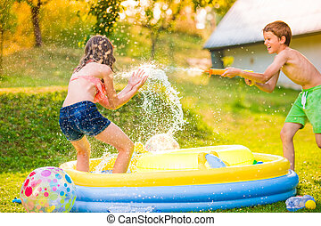 Boy splashing girl with water gun, garden swimming pool