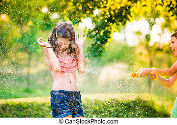Boy splashing girl with water gun, sunny summer garden