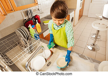 Boy sponging bowls under running water in the sink