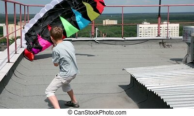 boy stand and hold shroud lines, parachute inflated by air -...
