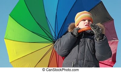 Boy stand and hold umbrella, he spins it by hook handle, kid is at center of screen