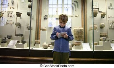 boy standing against clay exhibitions in museum
