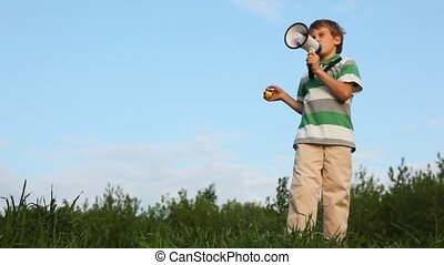 boy standing against sky, talking through megaphone and...