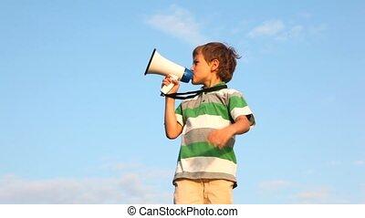 boy standing against sky, talking through megaphone