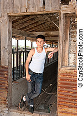 Boy standing at old barn