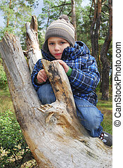 boy standing in the woods on a log.