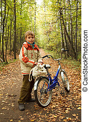 Boy standing next to a bicycle in the autumn park on the road strewn with yellow leaves.