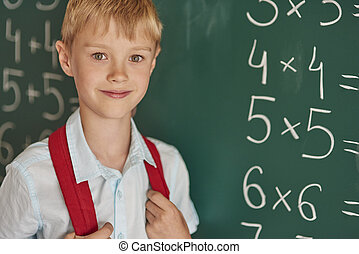 Boy standing next to the blackboard