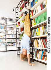 Boy standing on arms upside down in library