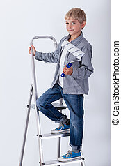 Boy standing on the ladder with paint roller