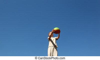 boy standing pop-up ball against blue sky
