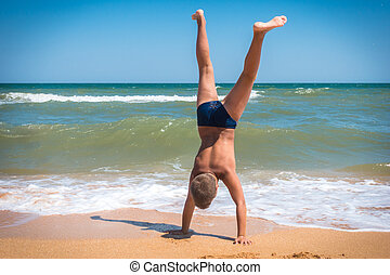 Boy standing upside down on the beach