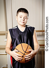 Boy standing with basketball closeup
