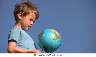 boy stands and looks at terrestrial globe