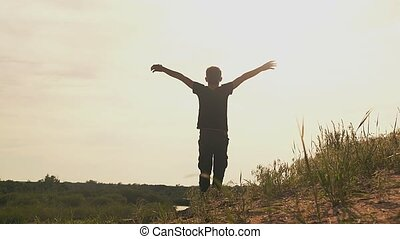 boy stands hands spread slow motion video - by the river boy...