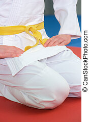 boy stands in white kimono with a yellow belt