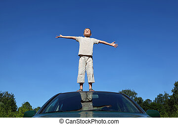 Boy stands on  head of auto  lifting  head to sky and conducts hands in sides