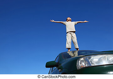 Boy stands on  head  of car widely placing hands and heaved up  face upwards on sky