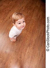 Boy stands on parquet - Little boy is standing on brown...