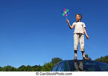 Boy stands on roof of car and holds windmill in hand