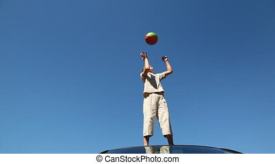 boy stands on roof of car and throws up ball