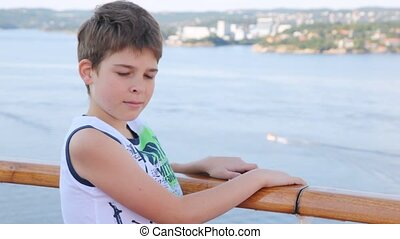 Boy stands on ship deck against sea and city in afternoon