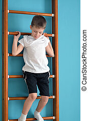 boy stands on the ladder before jumping