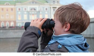 Boy stands on waterfront, looking through binoculars