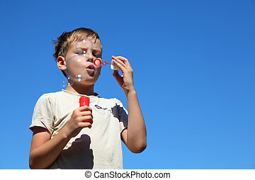 Boy stands straight and soap bubbles inflates