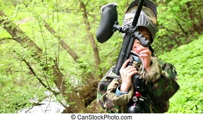 Boy stands with paintball gun at background of green leaves,...
