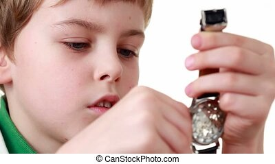 boy starts a wristlet watch on white - Little boy in shirt...