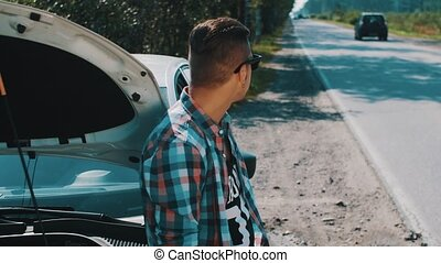Boy stay at broken car at road. Hitchhiking. Wait for help. Put off sunglasses