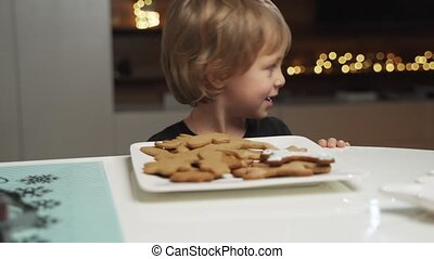 boy stealing a cookie while is mother is not watching.