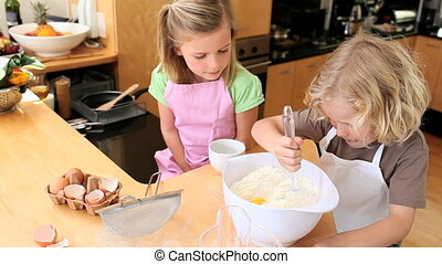 Boy stirring eggs with flour while his sister is looking